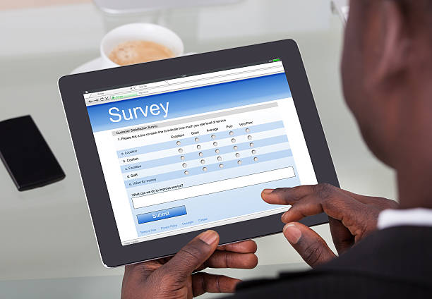 Businessperson Filling Survey Form On Digital Tablet Close-up Of A Businessperson Filling Survey Form On His Digital Tablet At Office questionnaire stock pictures, royalty-free photos & images
