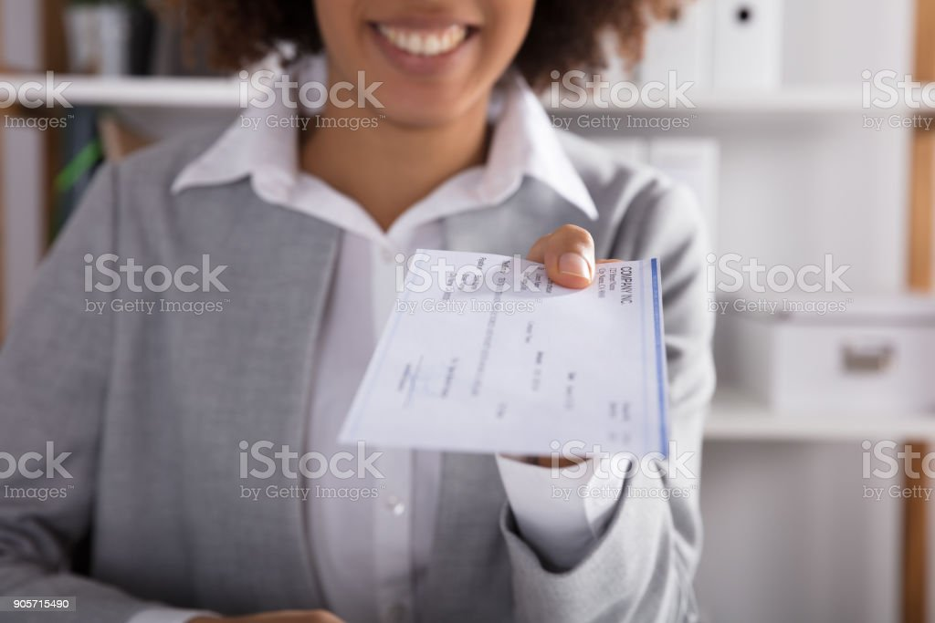 Businessperson Giving Cheque In Office stock photo