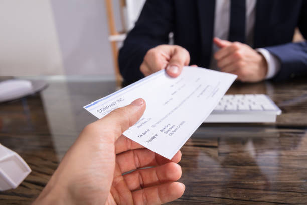 Businessperson Giving Cheque To Colleague stock photo