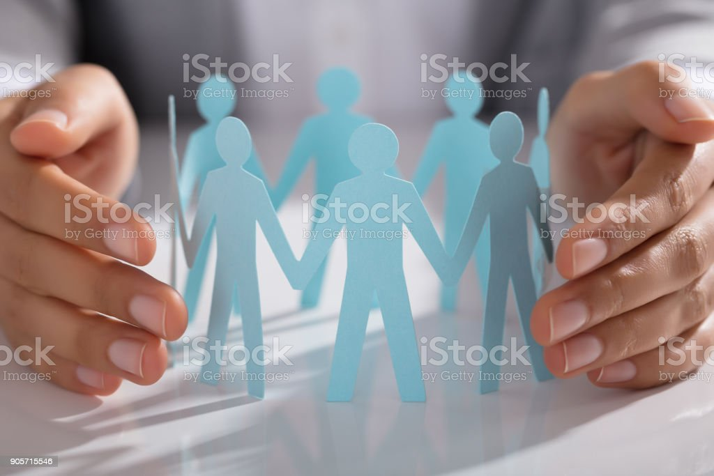 Businessperson Hand Protecting Paper Cut Out Figure On Table stock photo