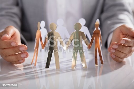 istock Businessperson Hand Protecting Paper Cut Out Figure On Table 905715548