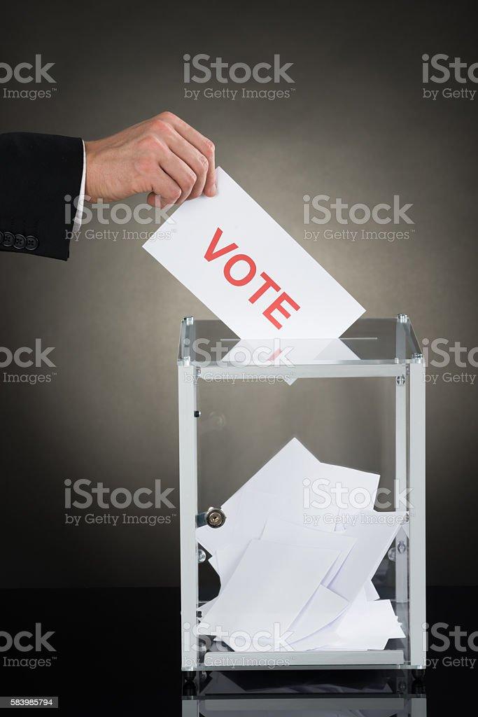 Businessperson Hand Putting Vote Into A Ballot Box stock photo