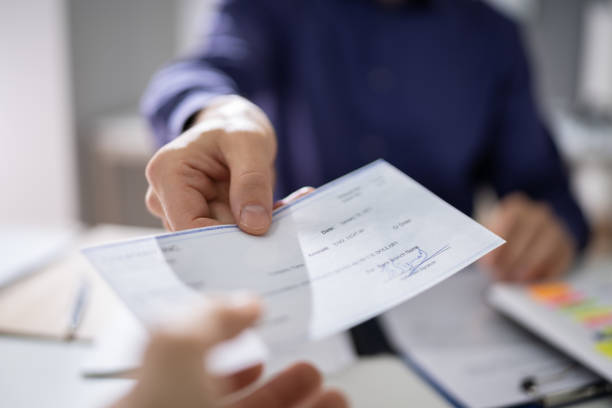 Businessperson Hands Giving Cheque stock photo