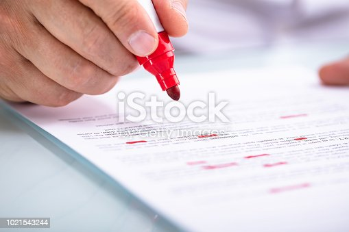 Close-up Of A Businessperson's Hand Holding Marker On Document