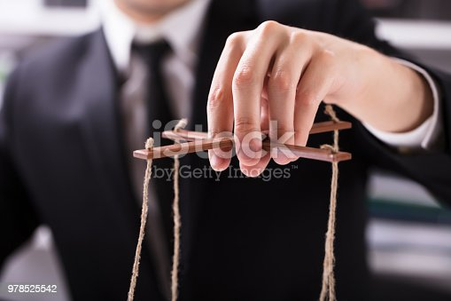 istock Businessperson Manipulating Marionette 978525542