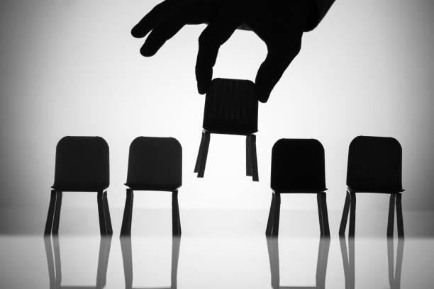 unternehmer, die abholung der stuhl unter anderem in einer reihe - abwesenheit stock-fotos und bilder