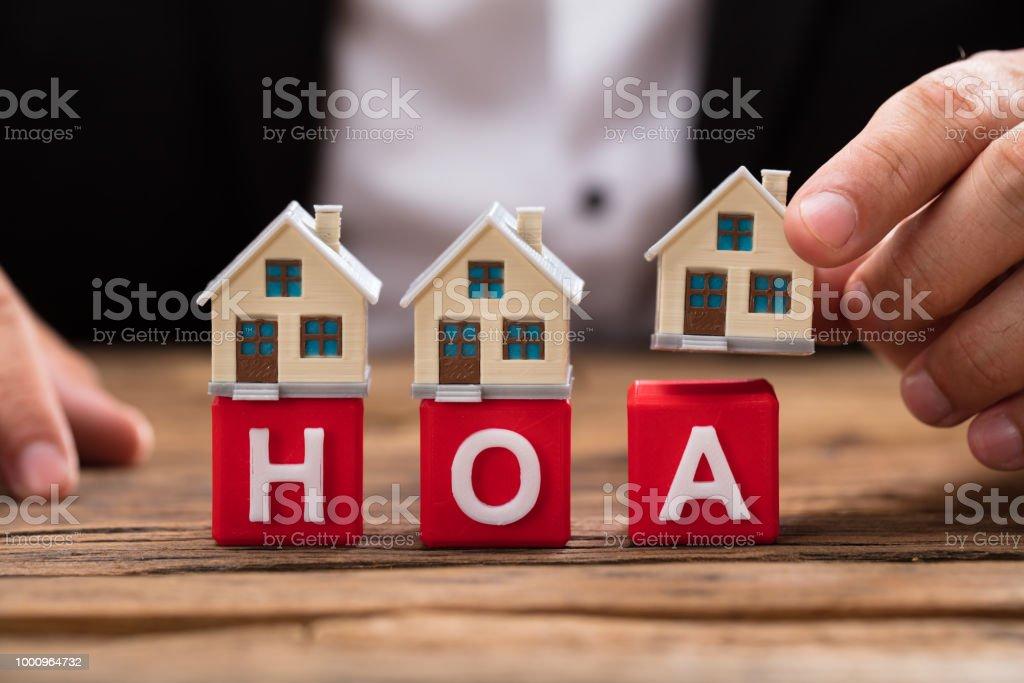 Businessperson placing house model over HOA blocks stock photo