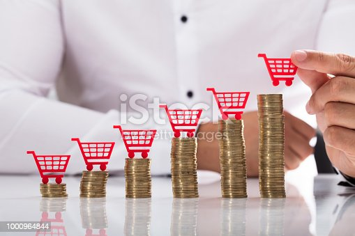 Businessperson's hand placing red shopping cart over increasing stacked coins