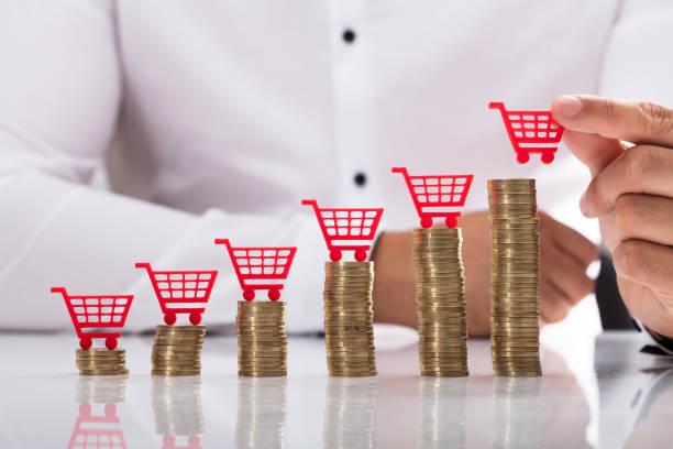 Unternehmer, die Platzierung Warenkorb über gestapelten Münzen – Foto