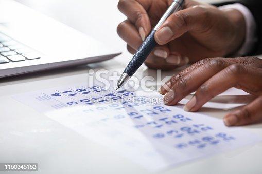 Businessperson Planning Agenda And Schedule Using Calendar Near Laptop In Office