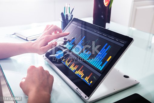 1044507110istockphoto Businessperson Pointing At Graph On Digital Laptop 1141353557