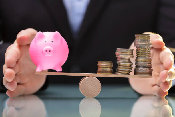 Businessperson Protecting Piggy Bank And Stacked Coins On Seesaw Businessperson's Hand Protecting Balance Between Piggy Bank And Stacked Coins On Seesaw 40 kilometre stock pictures, royalty-free photos & images
