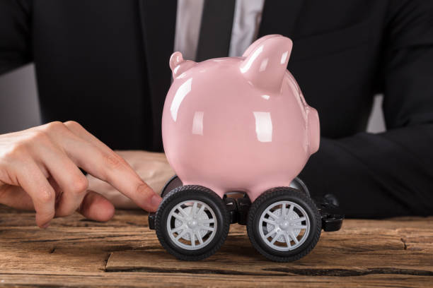 Businessperson Pushing Piggy Bank On Wheels Close-up Of Businessperson Pushing Pink Piggy Bank On Wheels At Desk 40 kilometre stock pictures, royalty-free photos & images
