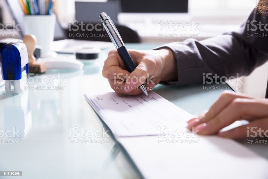 Businessperson Signing Cheque In Office stock photo