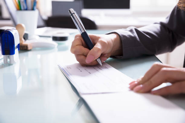 businessperson signing cheque in office - blank check stock photos and pictures