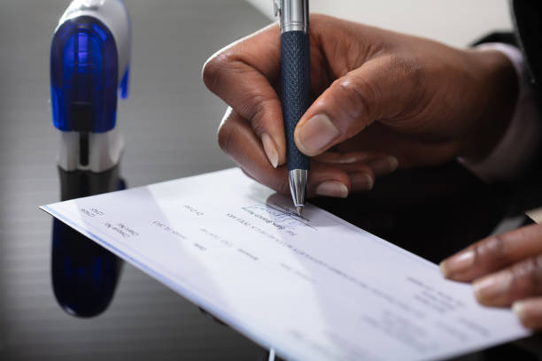 Businessperson Signing Cheque stock photo