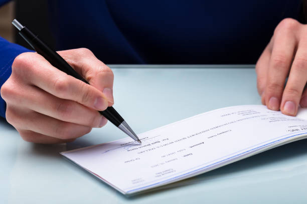 businessperson signing cheque - blank check stock photos and pictures
