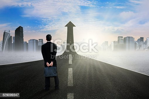 istock Businessperson standing on the road rising upward 529099347