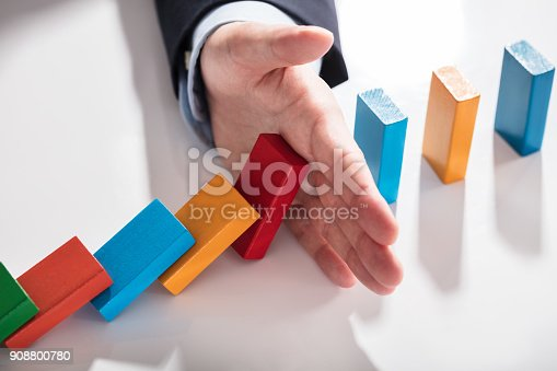 istock Businessperson Stopping Dominoes From Falling On Desk 908800780