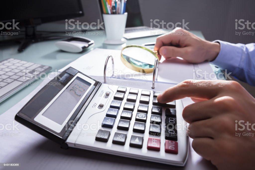 Businessperson Using Calculator For Calculating Bill stock photo