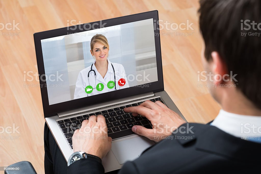 Businessperson Videochatting Online With Doctor On Laptop stock photo