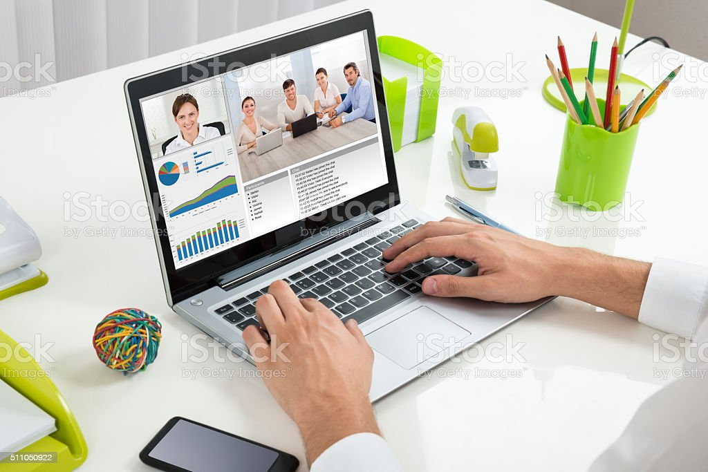Businessperson Videoconferencing With Colleagues On Laptop stock photo