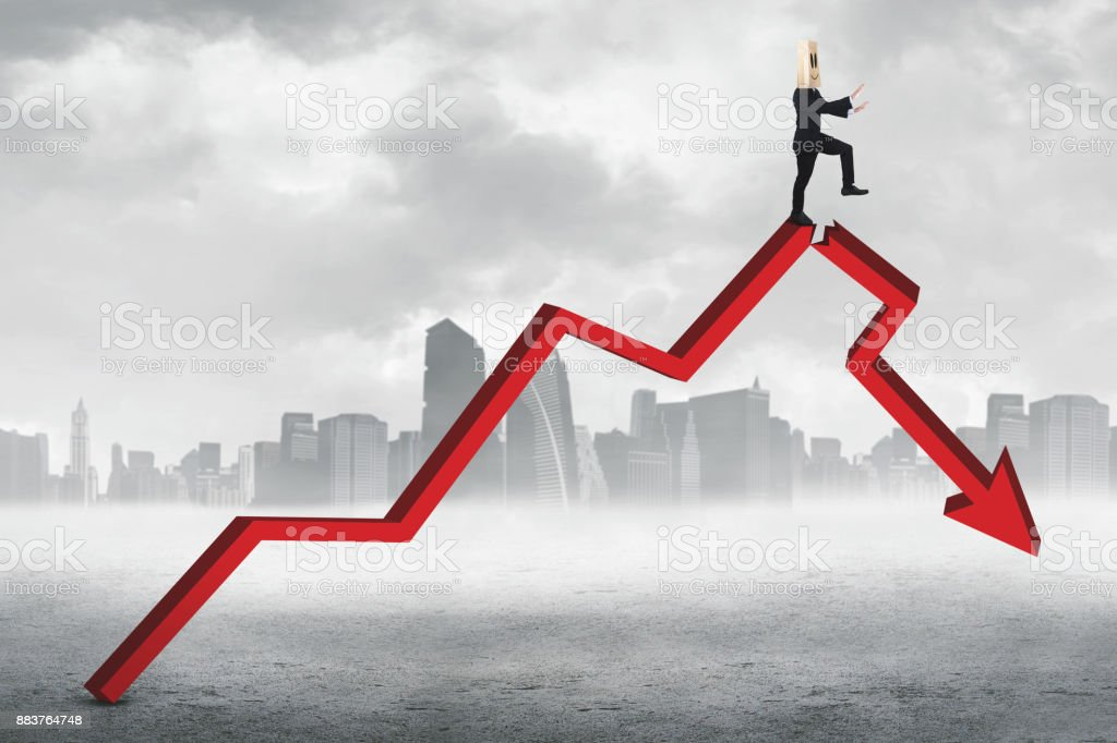 Businessperson walks on declining chart stock photo
