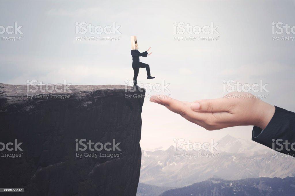 Businessperson walks toward a helping hand stock photo