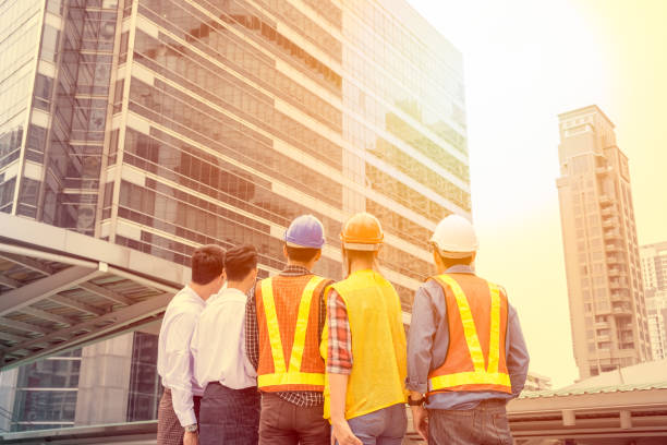 Businessperson with engineer group meeting agreement for construction and looking on skyscraper in the city Businessperson with engineer group meeting agreement for construction and looking on skyscraper in the city. Sunlight filter tone labor union stock pictures, royalty-free photos & images