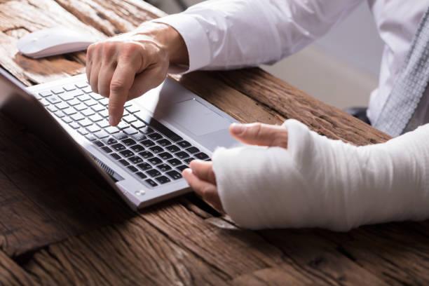 businessperson with hand injury using laptop - soddisfazione foto e immagini stock
