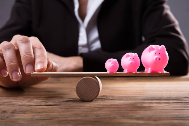 Businessperson's Finger Balancing Piggybanks On Seesaw Businessperson's Finger Balancing Pink Piggybanks On Seesaw Over Wooden Desk 40 kilometre stock pictures, royalty-free photos & images