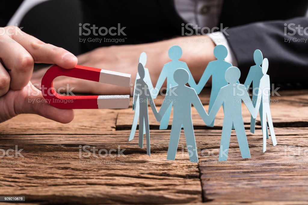 Businessperson's Hand Holding Horseshoe Magnet Attracting Leads stock photo