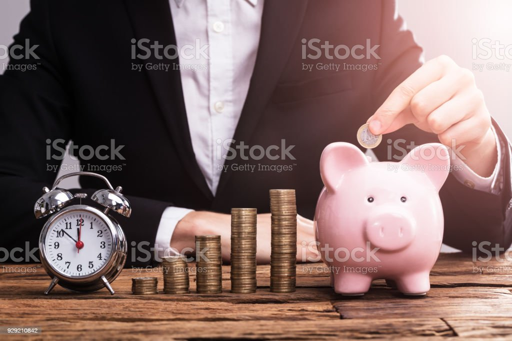 Businessperson's Hand Putting Coin In Piggybank stock photo