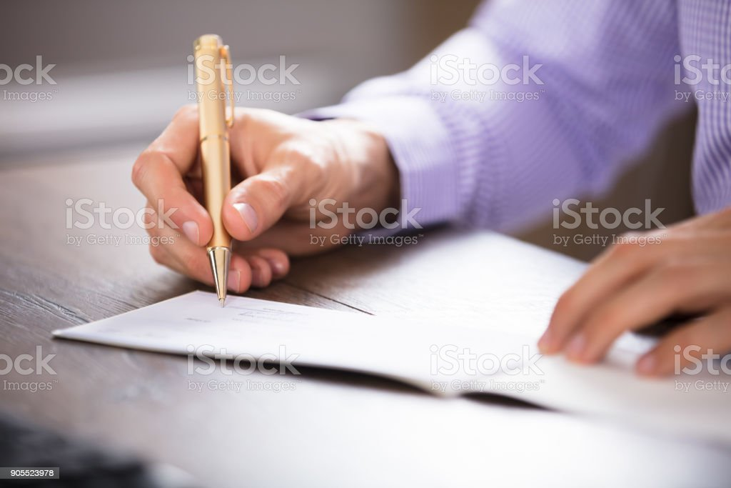 Businessperson's Hand Signing Cheque stock photo