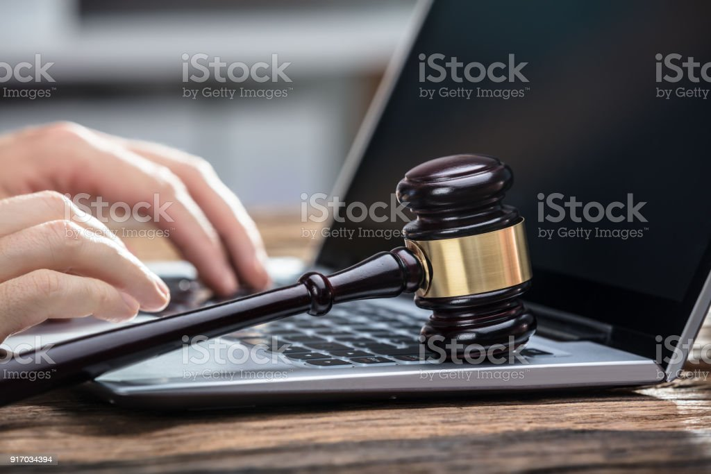 Businessperson's Hand Using Laptop On Wooden Desk Close-up Of A Businessperson's Hand Using Laptop With Gavel On Wooden Desk Auction Stock Photo