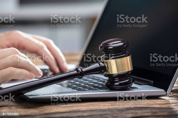 Businesspersons Hand Using Laptop On Wooden Desk Stock Photo - Download Image Now