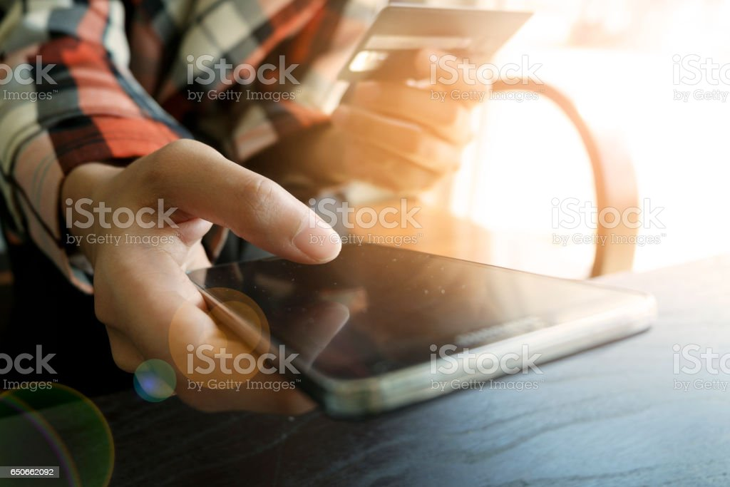 business's hands holding a credit card and using smart phone for online shoppin stock photo