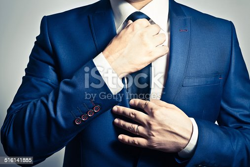 Businessman in blue suit adjusting his tie