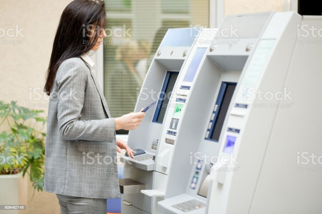 Businesswoma usin gATM machine stock photo