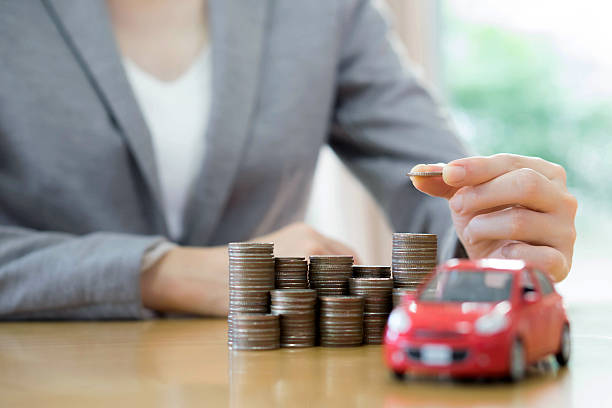 Businesswoman a toy car and a stack of coins stock photo