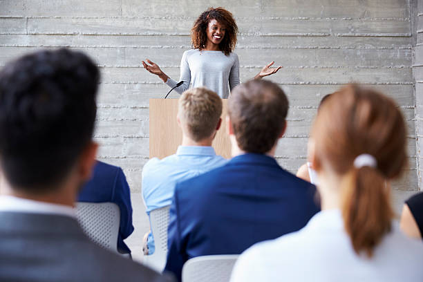 Businesswoman Addressing Delegates At Conference Businesswoman Addressing Delegates At Conference speech stock pictures, royalty-free photos & images
