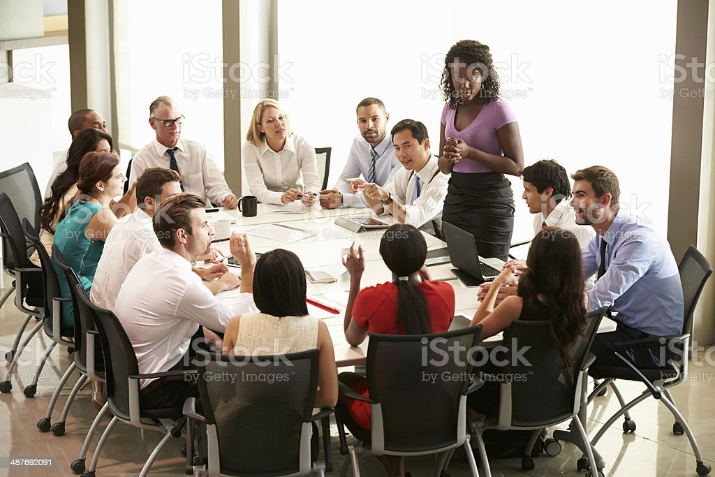 Businesswoman addressing others around board table stock photo