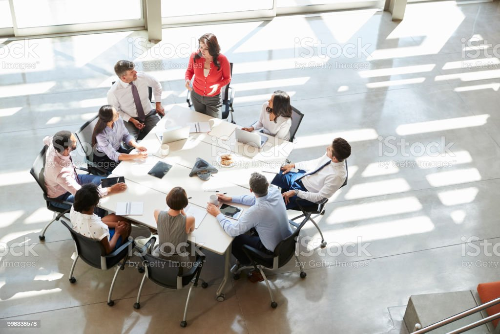 Businesswoman addressing team meeting, elevated view stock photo