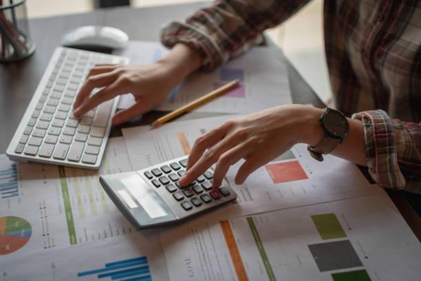 Empresaria analizar informes financieros con calculadora y digitar en el teclado de la computadora moderna en la oficina. Concepto de análisis de negocio. Contabilidad y la tecnología en la oficina. - foto de stock