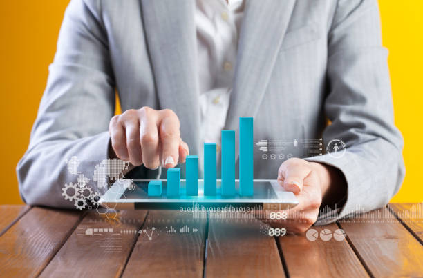 Businesswoman analyzing graph on digital tablet stock photo