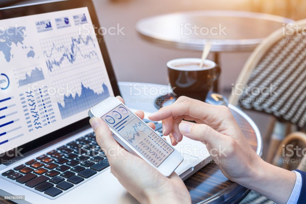 Businesswoman analyzing stock market KPI with BI, computer, smartphone screen stock photo