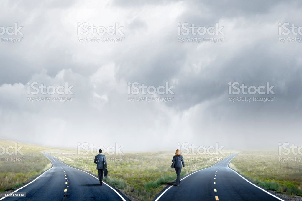 Businesswoman And A Businessman Take Separate Paths At A Fork In The Road stock photo