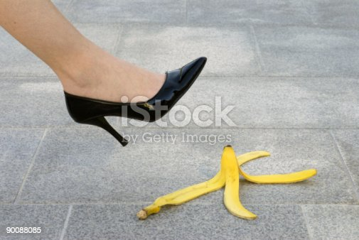 Businesswoman about to have an accident with a banana skin.  Alternative version shown below: