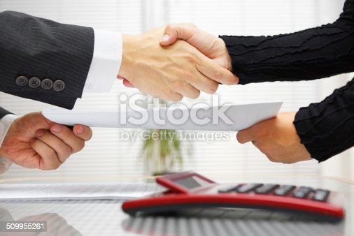 istock businesswoman and businessman are handshaking and exchanging contract documents 509955261