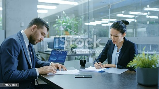 501040002istockphoto Businesswoman and Businessman Have Conversation. Draw up a Contract, Sign Documents, Seal the Deal, Finish Transaction, Come to an Agreement. They're in Modern Conference Room. 978271606